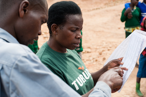 Assistant field director Mediatrice Musabyemaria (right) and field officer Yamuweli Nteziryimana (left) discuss and collect loan repayments in Gasovu, Rwanda. Photo by Hailey Tucker